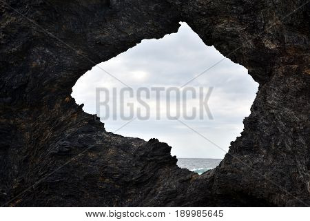Australia rock and ocean in Narooma. The shape of Australia cut into the rock wall was accidental and was created when a ship was tied to the rock with large chains to prevent it from washing away.