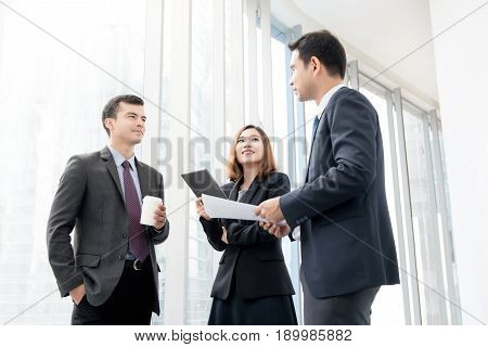 Group of business people meeting and discussing at office building hallway