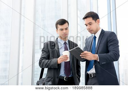 Two businessmen looking at tablet computer discussing work in office building hallway