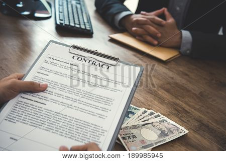 Businessman making contract with money Japanese yen banknotes on the table - loan bribery and corruption concepts