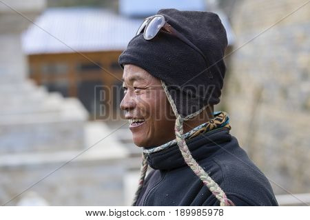 HIMALAYAS ANNAPURNA REGION NEPAL - OCTOBER 15 2016 : Portrait man in traditional dress in Himalayan village Nepal