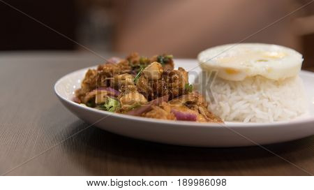 Fried chicken in spicy condiment salad with rice and fried egg serving in white dish at Thai restaurant