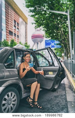 Business woman using phone app for mobile payment of ride share black cab car. Rideshare sharing concept. Asian businesswoman in financial district Pudong, Shanghai, China.