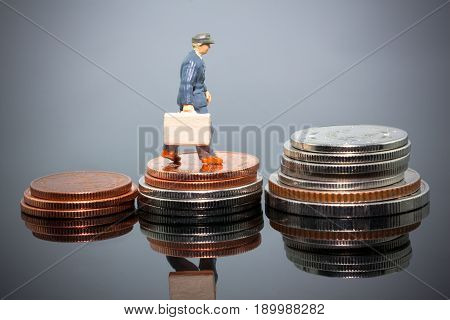 miniature businessman people walking on the coins financial concept