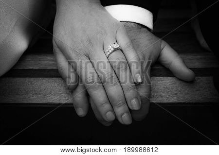 Newl-wed's holding hands. Woman showing off engagement Ring