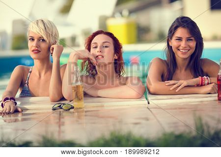 Young attractive blonde, brunette and red haired female bathers posing on edge of swimming pool at summer