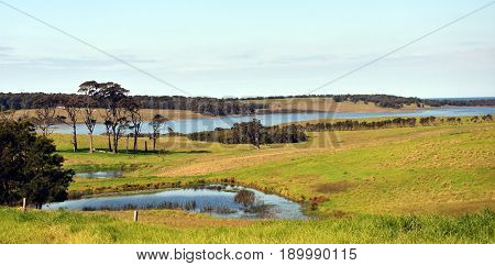 Central Tilba in its idyllic setting near Narooma. Autumn scene in rural New South Wales Australia. Farmland fields trees ponds and hills.