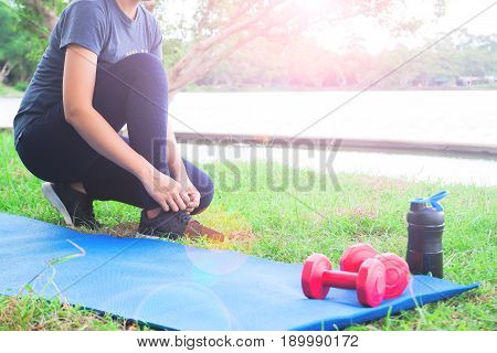 Asian woman in sport clothing tying shoes getting ready for exercice in park Workout and Healthy lifestyle concept