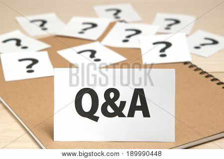 Q&A or Questions and Answers on a piece of paper and many question marks on notebook. Q&A concept.