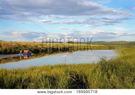 Country landscape. Soroti river and motor boat with tourists near the Mikhailovskoye village Pskov region Russia. Summer evening.