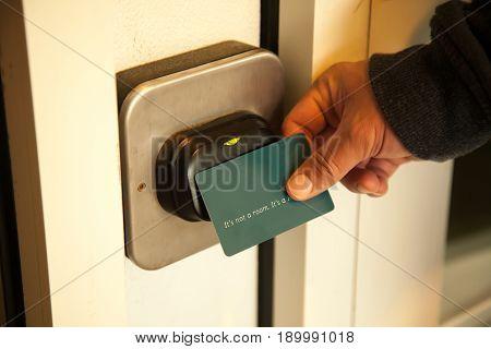 Traveler opening hotel room door by plastic keycard.