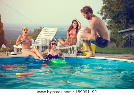 Male jump style bomb in open pool while girls admires him