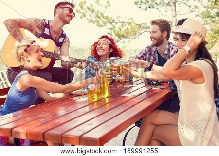 Joyful youngsters play guitar and toasts with glasses of beer in nature