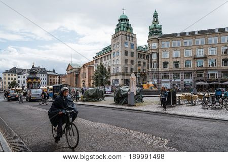 Copenhagen Denmark - August 10 2016. Cityscape of historical city centre of Copenhagen with old woman riding a bicycle. The bicycle is the typical mode of transport in Denmark