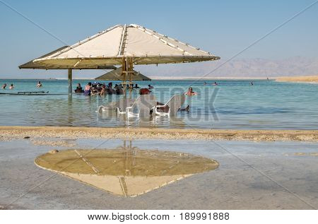 Tourists Take Salt Bath In Dead Sea Under Umbrella Reflected In Water
