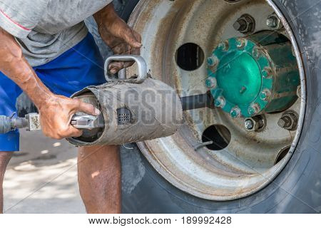 The grungy man worker using mechanical equipment tightening lug nuts of big truck tyre.