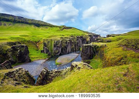 Green Icelandic Tundra in July. Fast river with glacial water flows among cliffs. Magic canyon Fyadrarglyufur. The concept of active northern tourism