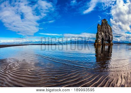 Rock Hvitserkur on the sea beach in the form of a huge elephant. Ocean tide at sunset. The north coast of Iceland. The concept of northern extreme tourism