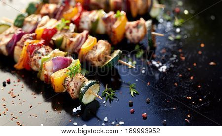 Grilled meat and vegetable skewers with fresh herbs and spices, dark background