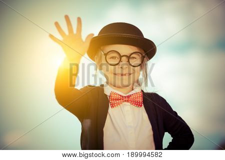 Funny little girl in bow tie and bowler hat with hello gesture. Retro stile.