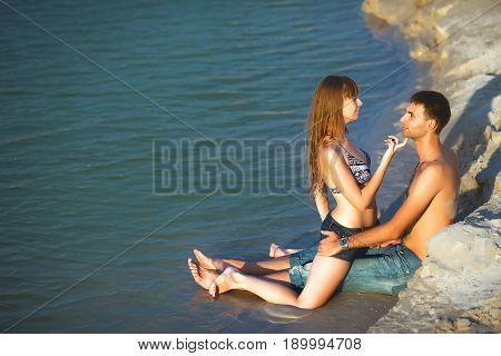 Beach lovers on romantic travel honeymoon vacation summer holidays romance. in love girl and man looking in each other on ocean shore