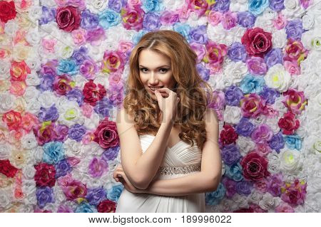 Beautiful woman smiling, wearing a wedding dress, on a background of flowers. Emotion shyness