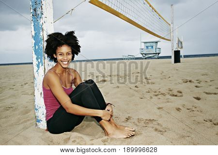 Mixed race woman sitting by volleyball net on beach