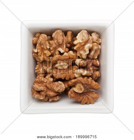 Roasted walnuts in a square bowl isolated on white background