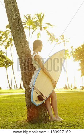 Pacific Islander woman carrying surfboard