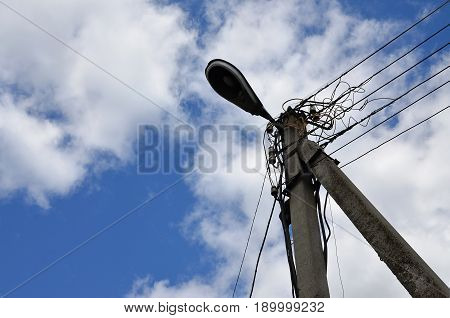 Old Concrete Electric Pole For Transmission Of Wired Electricity With Lamp Post On A Background Of A