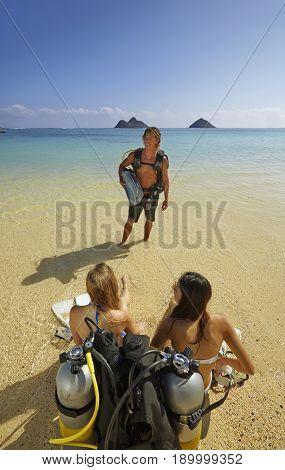 Friends with scuba gear on beach