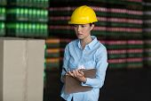 Attentive female factory worker maintaining record on clipboard in factory poster