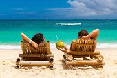 Beach summer couple on island vacation holiday relax in the sun on their deck chairs on the tropical beach. Idyllic travel background. poster