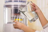 Close up of a woman holding a glass of water in one hand and a pitcher of water in her other hand, with a filter system of water purifier on a kitchen background. poster
