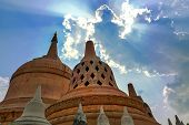 Sunrays shining through clouds above Chedi Hin Sai a huge complex of sandstone stupas resembling Borobudur at Wat Pa Kung Temple in Si Somdet district Roi Et northeastern Thailand poster