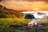 campfire and tent at sunrise. View of tourist tent on green meadow. Camping background. Adventure travel active lifestyle freedom concept. Summer landscape. Foggy meadow in the sunny beams poster