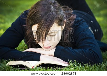 Beautiful brunette woman reading on the grass