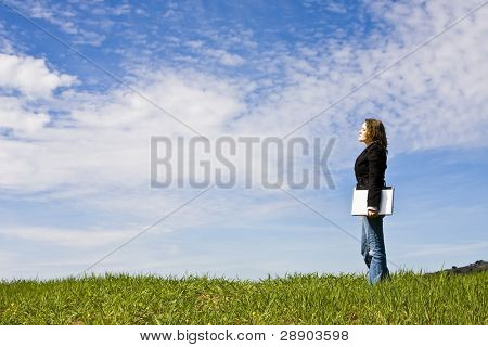 Young woman with laptop in meadow, coy space.