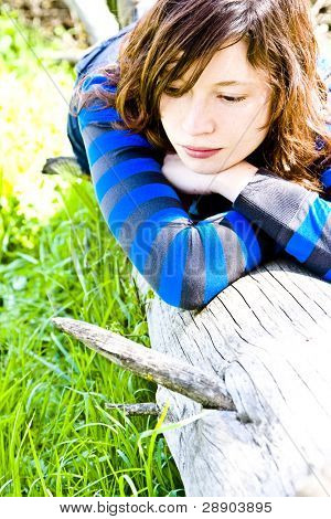 Young woman resting on a tree trunk. Old color style.