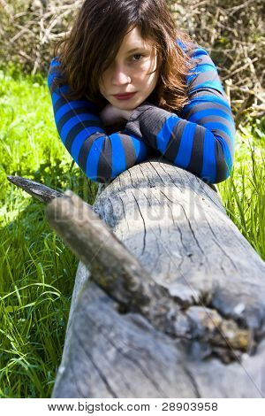 Young woman resting on a tree trunk.