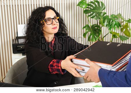 Business Woman Gets A Stack With Documents. Business Documents Concept. Accountant At Workplace In O