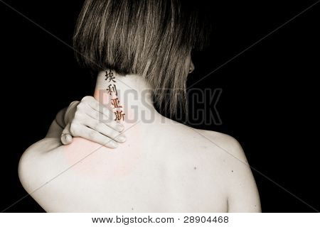 Short haired woman with asian tattoo in her neck feeling pain.