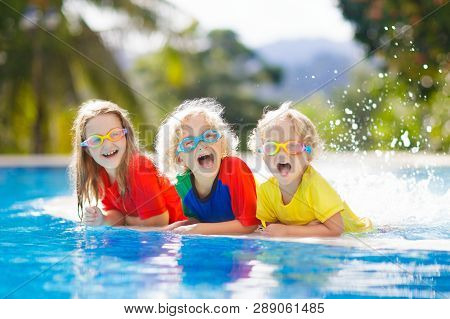 Kids Play In Swimming Pool. Children Learn To Swim In Outdoor Pool Of Tropical Resort During Family