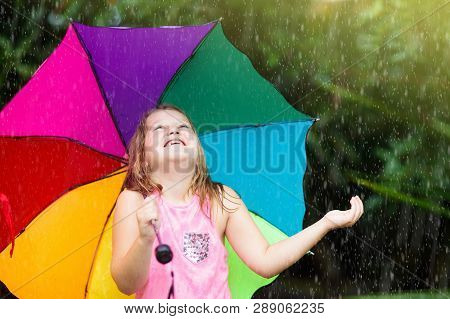 Kid With Umbrella Playing In Summer Rain.