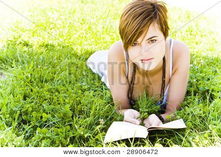 Beautiful blond woman reading over the grass.
