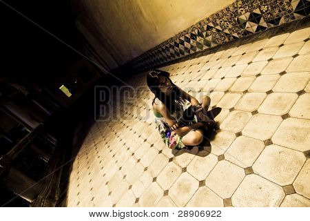 Young woman sited on the sanitarium floor.