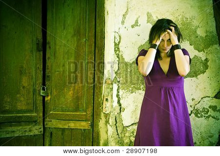 Disturbed young woman over cracked old wall.