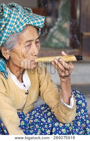 Bagan, Myanmar - January 17, 2017: An 93-year Old Woman Is Smoking A Cigar In Her Leasure Time After