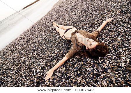 Crucified woman in stone beach, long exposure