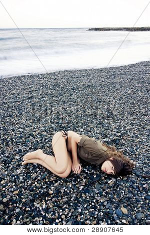 Beautiful woman laying on the beach with sad gesture. Long exposed waves.